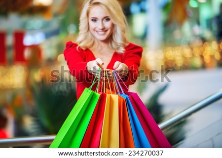 Young woman with colored shopping bags in the shopping mall on sales. Focus on the hands and bags - stock photo