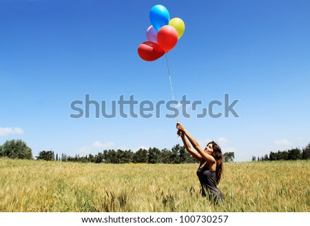 Young woman with colorful balloons in the field - stock photo