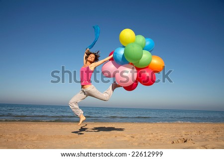 young woman with colorful balloons on the beach - stock photo