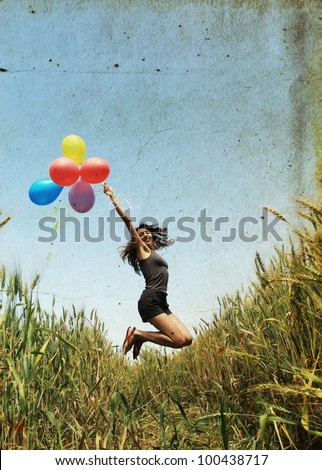 Young woman with colorful balloons. Photo in old color image style. - stock photo