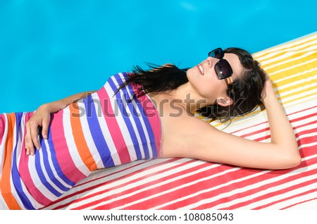Young woman with colorful dress and sunglasses lying and sunbathing at poolside on blue water background in a hot summer day. - stock photo