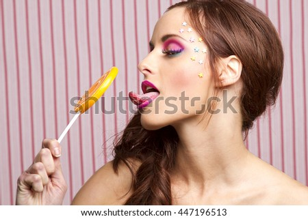 Young woman with colorful makeup and star candy glued to her face, licking an orange lollipop - stock photo