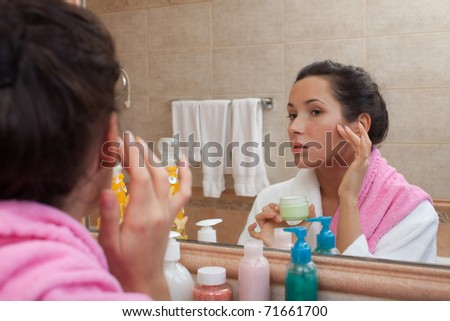 Young woman with cosmetic cream in a bathroom. Concept body care. - stock photo