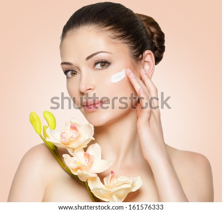 Young woman with cosmetic  cream on a clean fresh face. Healthy lifestyle concept - stock photo