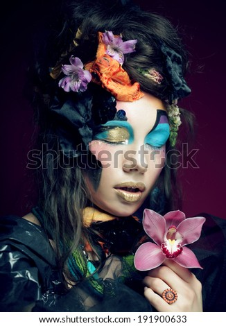 young woman with creative make up holding pink flower - stock photo