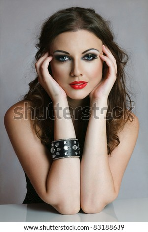 Young woman with creative makeup touching her face - stock photo