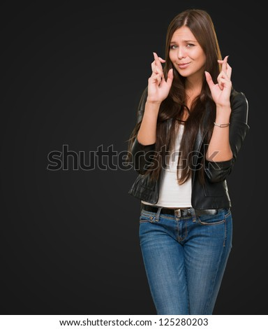 Young Woman With Crossed Fingers against a black background - stock photo