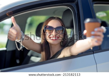 Young woman with cup of coffee showing okay out of the car window - stock photo