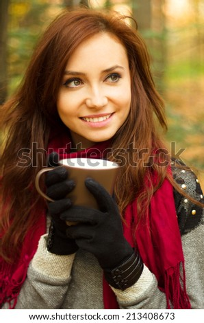 Young woman with cup of tea in autumn park - stock photo