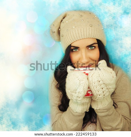 Young woman with cup on winter holiday background. - stock photo