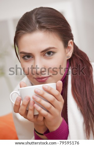young woman with cup tea relaxed at home - stock photo