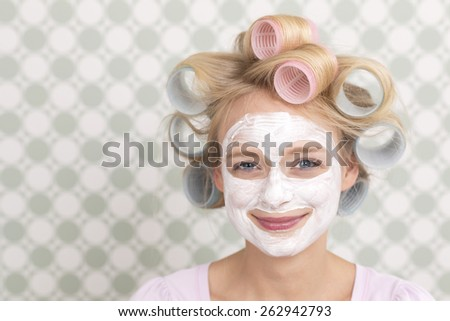 Young woman with curlers and face mask, smiling - stock photo
