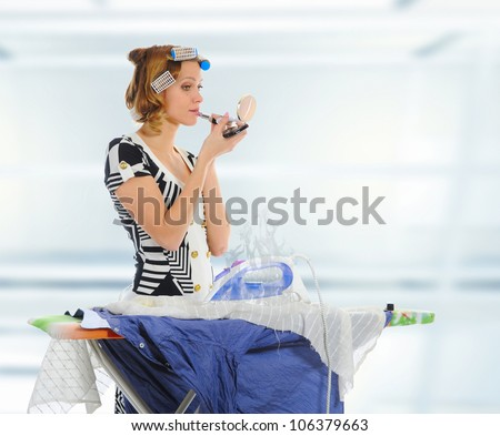 Young woman with curlers on her head stroking men shirt makes makeup. - stock photo