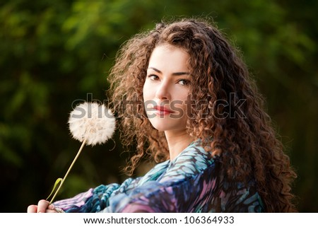 young woman with curly hair hold butter cup flower outdoor portrait - stock photo
