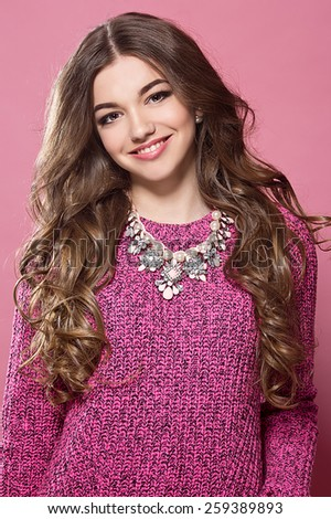 young woman with curly hair in a pink sweater - stock photo