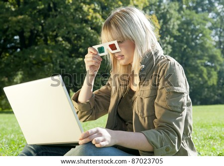 young woman with 3D-glasses and laptop on a meadow - stock photo