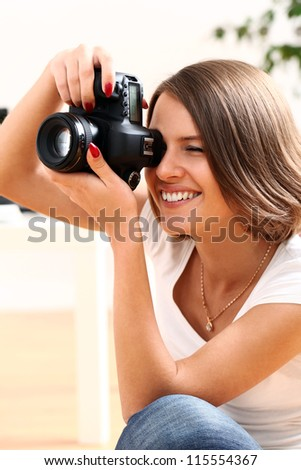 Young woman with digital photo camera at home - stock photo