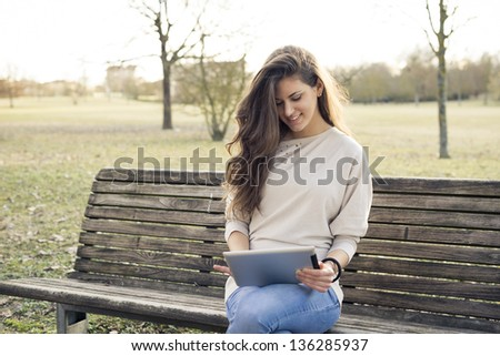 young woman with digital tablet at the park - stock photo