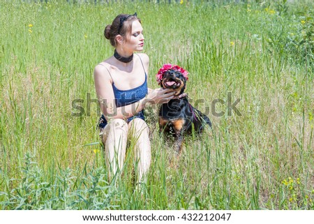 Young woman with dog sitting in the grass in a meadow - stock photo