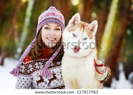Young woman with dog winter outdoors fun - stock photo