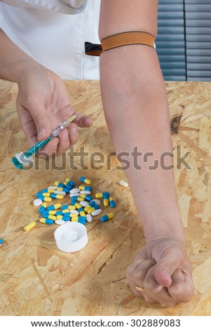 Young woman with drug addiction, pills and syringe - stock photo
