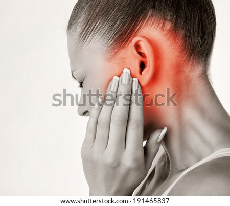 Young woman with ear pain, holding hand on his head on white background - stock photo