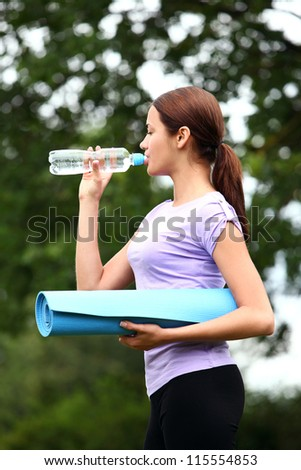 Young  woman with fitness mat and bottle of fresh water in the park - stock photo
