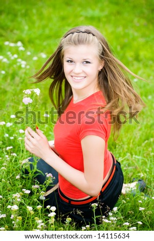 Young woman with flowers in a meadow. - stock photo