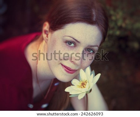 Young woman with freckles on face holding lily flower. Soft calm portrait. - stock photo