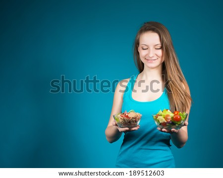 Young Woman With Fresh Salad And Cereal On Blue Background. - stock photo
