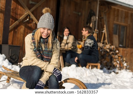 Young woman with friends enjoy weekend break snow winter cottage - stock photo