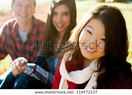 Young woman with friends in the background smiling - stock photo