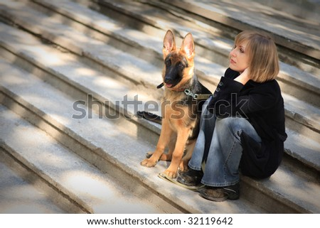Young woman with german shepherd puppy - stock photo