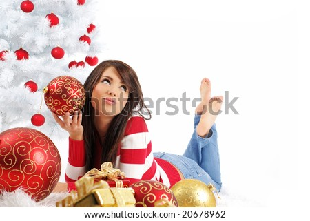 young woman with gift box next to white christmas tree - stock photo