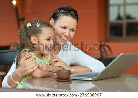 Young woman with girl using laptop computer - stock photo