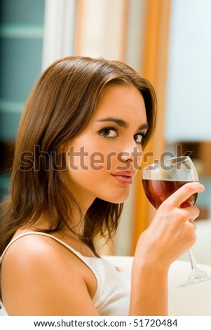 Young woman with glass of red wine, indoors - stock photo