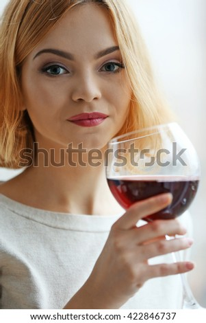 Young woman with glass of red wine on light blurred background - stock photo