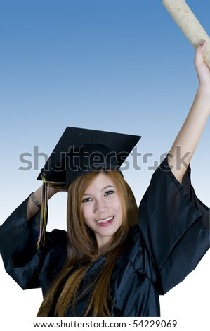Young woman with graduation cap and gown holding diploma in the air - stock photo