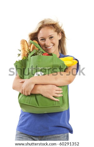 Young woman with green recycled grocery bag of healthy food and vegetables - stock photo