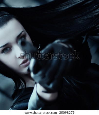Young woman with gun wearing gloves - stock photo