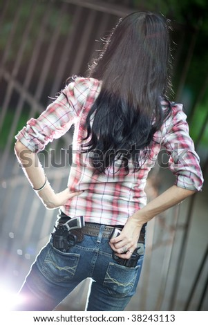 Young woman with guns backside view. Shallow dof and light flash effect. - stock photo
