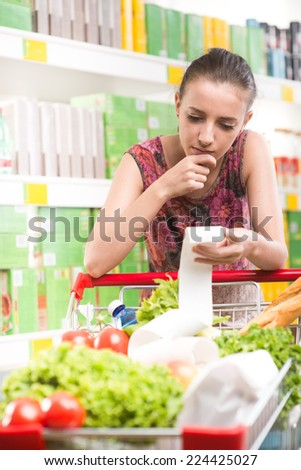 Young woman with hand on chin examining a grocery receipt at supermarket leaning to a shopping cart. - stock photo