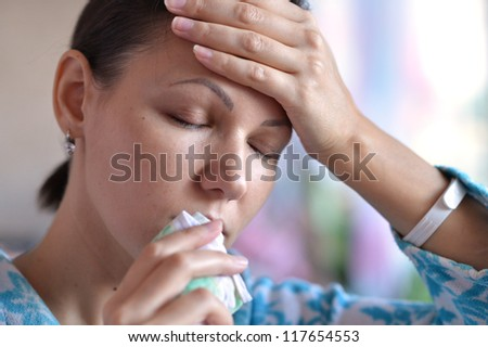 Young woman with handkerchief having cold with fever - stock photo