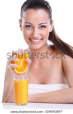 young woman with  hands squeezing out half of orange into the glass with orange juice - stock photo