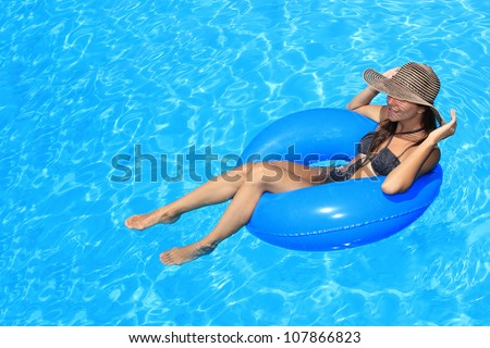 Young woman with hat enjoying a swimming pool - stock photo