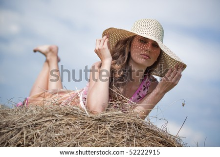 Young woman with hat lying on haystack. - stock photo