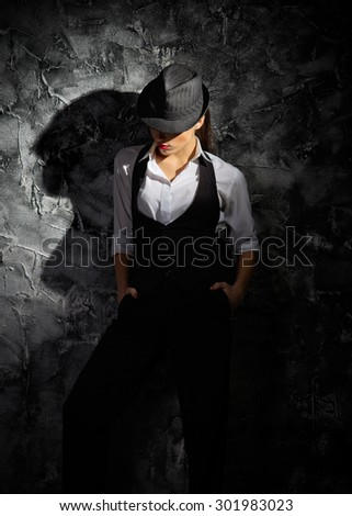 Young woman with hat on grey wall - stock photo