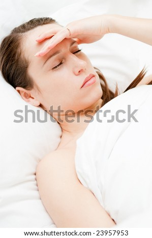 young woman with headache in her bed - stock photo