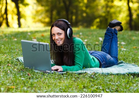 Young woman with headphones is using her laptop while lying down in the nature,Woman  with headphones using laptop - stock photo