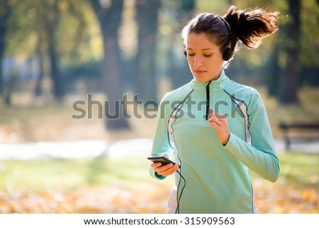 Young woman with headphones jogging in autumn nature and looking to mobile phone - stock photo